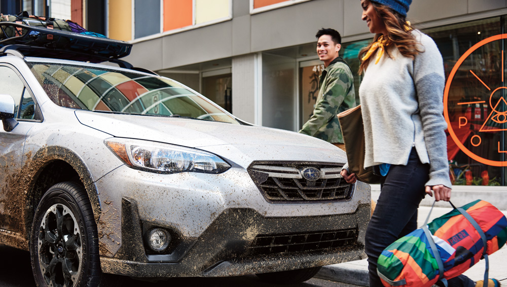 A Young Couple Standing In Front Of 2021 SUBARU Crosstrek